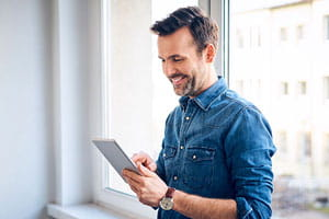 Smiling man using tablet at the window